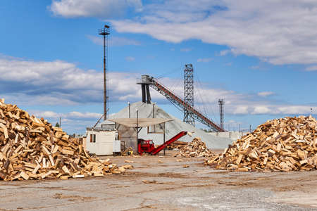 modern firewood processor in operation in the yard of a woodworking factory