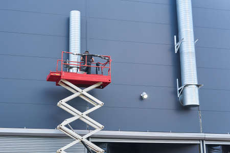 worker installs a ventilation system on the facade of a building using a scissor lift