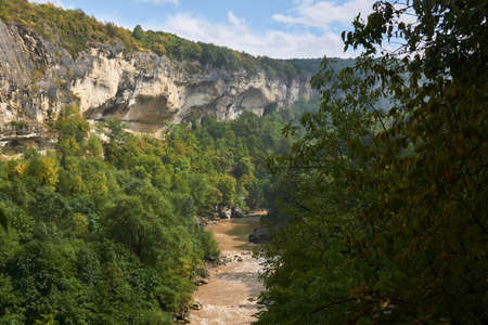 rocky canyon with a muddy mountain river at the bottom among the autumn forest