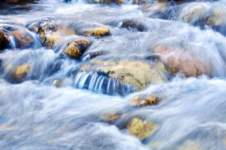 cascade of small waterfalls of a mountain river among the boulders, the water is blurred in motion