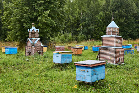 Perm, Russia - August 13, 2020: vintage hives in the form of temples among ordinary hives in a forest apiary