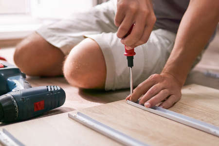 man assembles furniture by hand at home, sitting on the floor, only hands with a screwdriver in focus