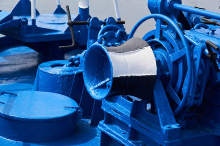anchor windlass, capstan and other mechanisms, painted blue, on the foredeck of the ship, close-up