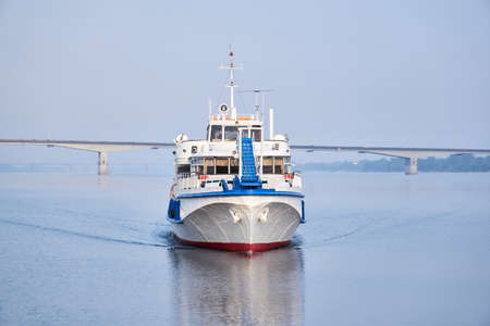 small passenger motorship on the river, front view, and a road bridge in the morning haze in the background