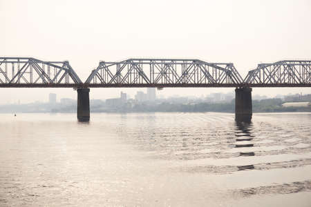 road bridge over a wide river and the silhouette of a distant city behind it in the morning haze