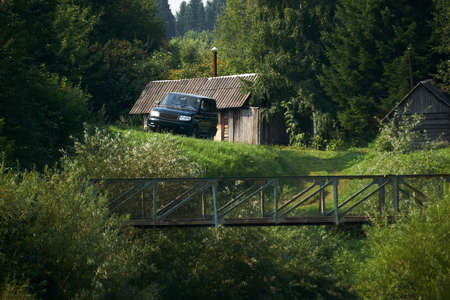 rural landscape, a lonely homestead in the forest - a log cabin, a bathhouse and an off road vehicle on the edge of a ravine with a bridge