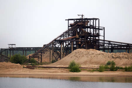 huge stationary rusty separator of sand and gravel on the shore of the reservoir