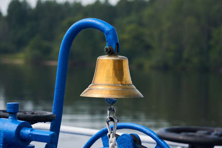 brass bell on the foredeck of a ship, close-up against the background of a blurred wooded coast