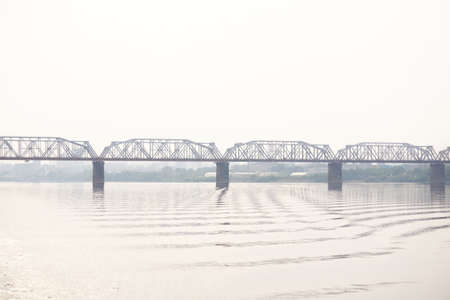 railroad bridge over a wide river and the silhouette of a distant city behind it in the morning haze