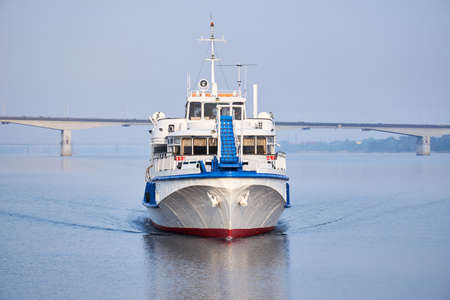 small passenger ship on the river, front view, and a road bridge in the morning haze in the background