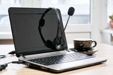laptop, headphones with microphone and coffee cup on the table close up