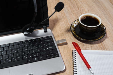 laptop, headphones with microphone, notebook with pen and coffee cup on the table close up