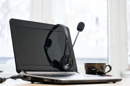 Laptop with headphones, microphone and coffee cup on the table Reklamní fotografie
