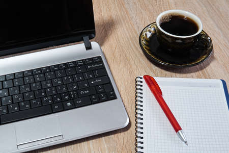 Laptop, paper notebook with pen and coffee cup on the table