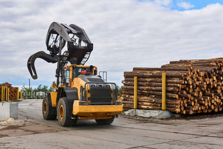 wheeled grapple loader in the timber yard of a woodworking plant