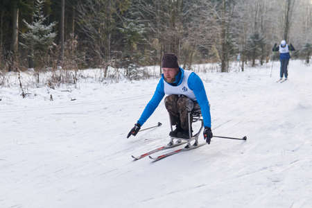 Perm, Russia - December 12, 2020: athlete with a disabilitiy participates in cross-country sit-skis competition on a track in the forest