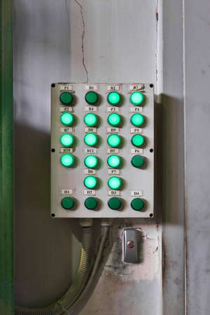 shabby control panel for some industrial processes with luminous buttons hangs on the wall in the workshop