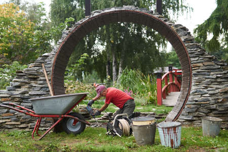 Perm, Russia - September 01, 2020: worker builds a round entrance called a moon gate in a Chinese-style garden
