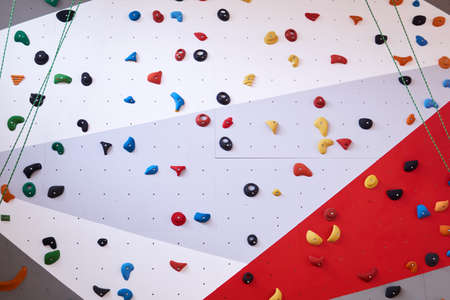 background - multi-colored climbing wall with grips for hands and feet
