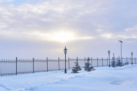 winter snow-covered park with a fence, lanterns, fir trees and sunlight shining through the clouds