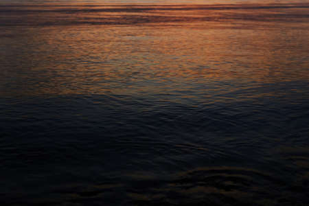 dark water surface with a reflection of a distant dawn