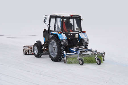 wheeled tractor with a snow plow and a mechanical sweeper moves on a snowy background Reklamní fotografie
