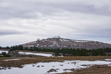 white domes of the radar complex on a hilltop on a cold plateau