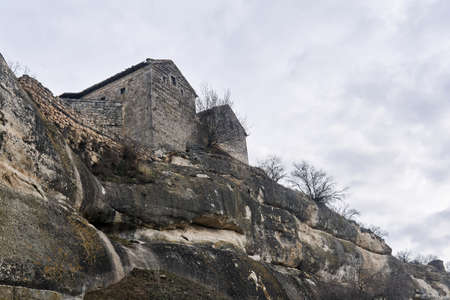 view of the Karaite kenassas on the edge of a cliff in the ancient cave city-fortress of Chufut-Kale, Crimea