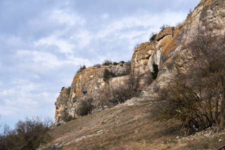 winter terrain of central Crimea with rocky cliffs at the edge of the cuesta and ancient fortress wall between the rocks
