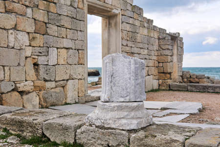 fragment of a marble column among the ruins of antique greek temple on the seashore 스톡 콘텐츠