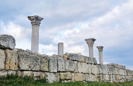 ruins of the wall of an ancient Greek temple with columns against the sky 스톡 콘텐츠