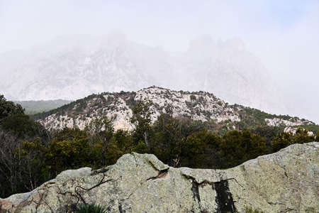 mountain range in the clouds is barely visible behind the rocks on the foreground