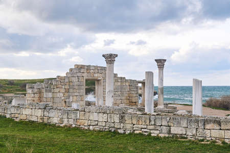 ruins of an ancient basilica with columns against the background of the sea surf on the nearby shore