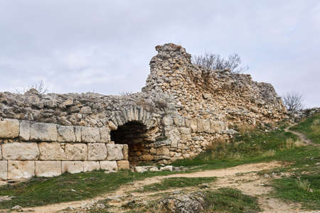 dilapidated antique wall with arch and masonry from different centuries