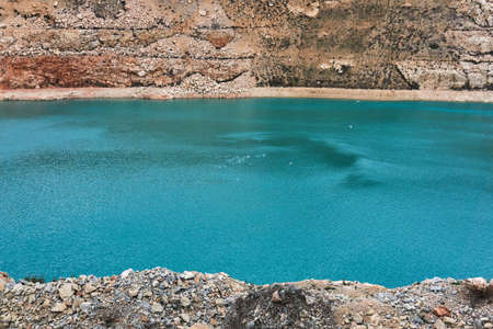 stepped slopes of an old limestone quarry with a blue lake with seagulls at the bottom 스톡 콘텐츠