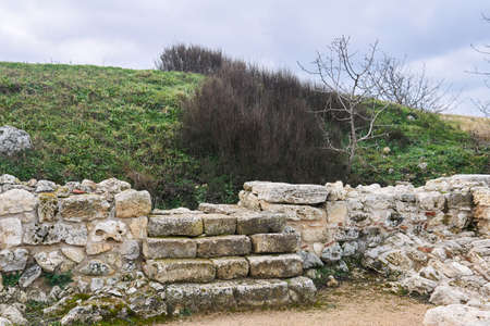 stone steps in the ruins of an antique house lead to an unexcavated part of it under the hill