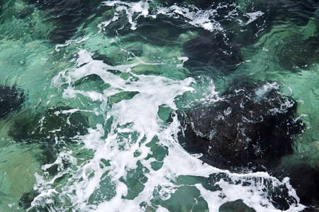 clear coastal sea waters with waves and foam, top view