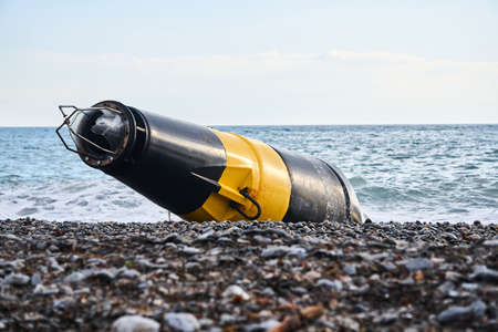 damaged black and yellow sea buoy (cardinal danger mark) washed ashore after a storm 스톡 콘텐츠