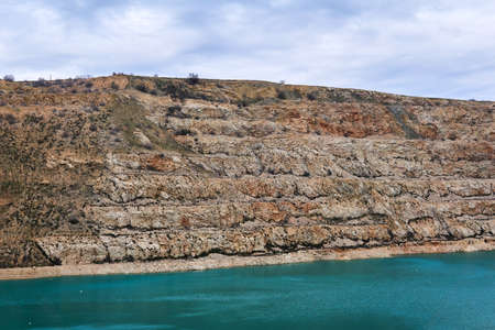 slopes of an old limestone quarry with a blue lake at the bottom