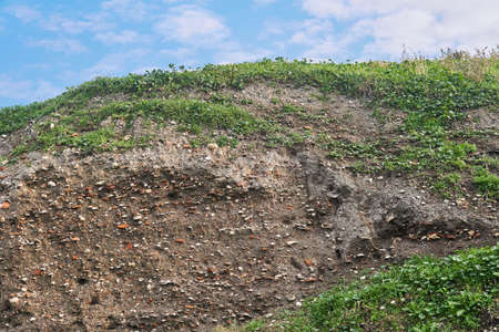 occupation earth - deposits under a layer of turf at the site of an ancient settlement, containing shells and pottery shards