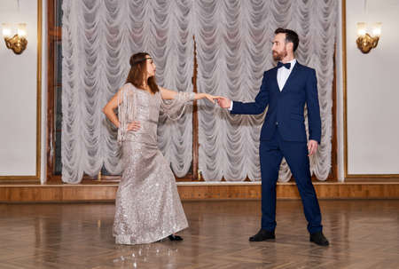 couple dancers before the start of a partner dance in the vintage hall; dance invitation 스톡 콘텐츠