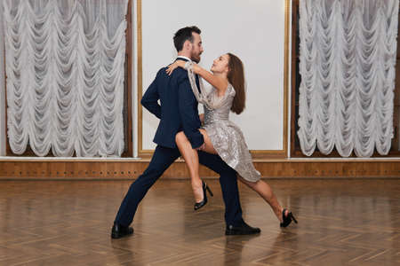 dance training, man and woman with feeling practice tango dance elements in the ballroom