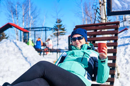 woman with a cup of hot drink lies in a sun lounger outdoors on a cold winter day against the backdrop of a blurred snowy park landscape 版權商用圖片