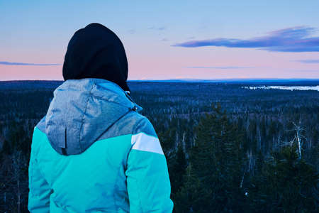 female hiker looking from hilltop at cold morning winter forest landscape 版權商用圖片