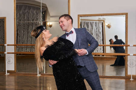man and woman amateur dancers laugh during classical dance with each other