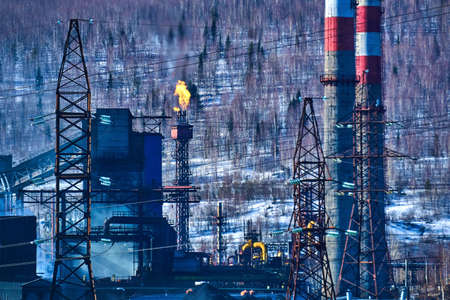 industrial background - the torch of a coke-chemical plant produces thermal emissions into the atmosphere against the background of a winter landscape 版權商用圖片