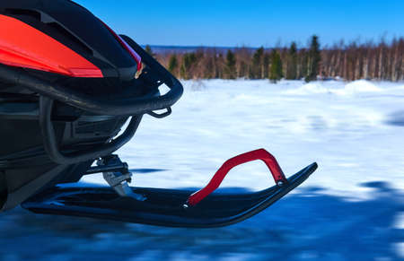 front ski of the snowmobile while driving on a snowy winter landscape