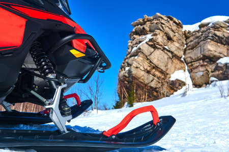 snowmobile close up on blurred mountain winter landscape background
