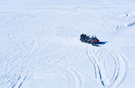 snowmobile on a snowy field with traces of many snowmachines, top view
