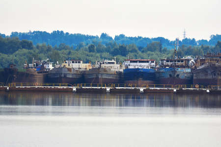 old cargo and work ships, prepared for disassembly and cutting into metal, in the river harbor